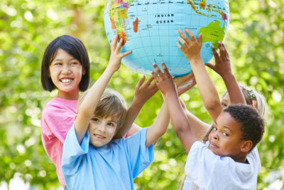 a group of children holding the globe and smiling