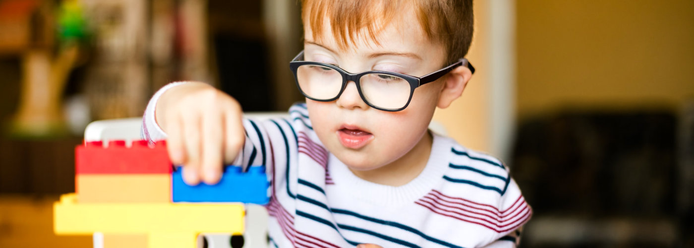 boy with black glasses playing with colorful blocks